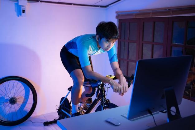 Azjatycki człowiek na rowerze na trenerze maszyn, który ćwiczy w domu w nocy. gra online na rowerze