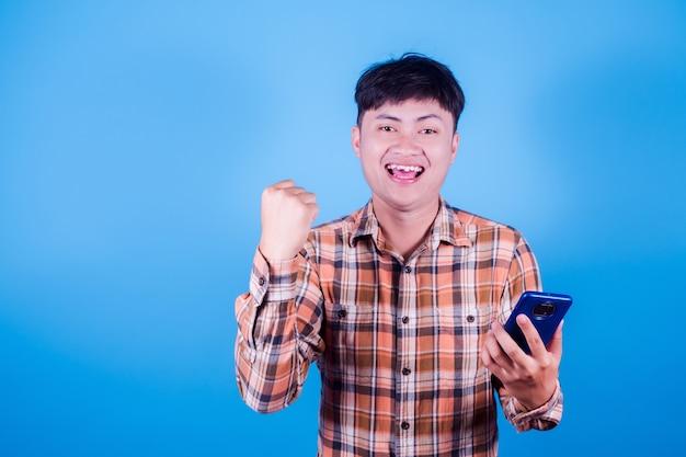 Azjatycki człowiek na telefon i patrząc na kamery ze zdumieniem na niebieskim tle. człowiek pokazuje zwycięski gest, podnosząc rękę.