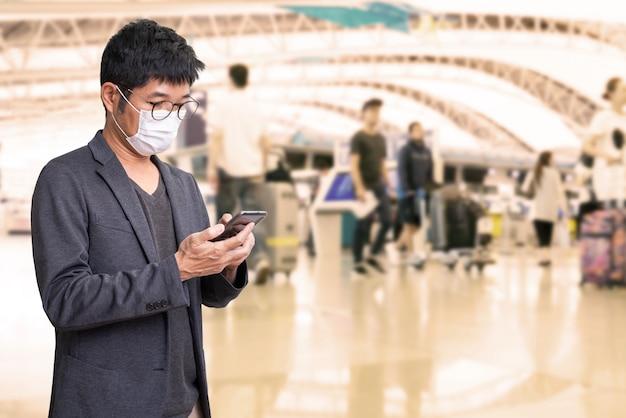 Azjatycki człowiek nosi maskę chirurgiczną, aby zapobiec coronavirus choroby grypy i za pomocą telefonu komórkowego