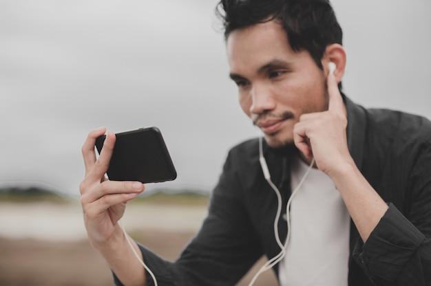 Azjatycki człowiek oddalenie społeczne wideokonferencja rozmowa wideo na internet smartfonie