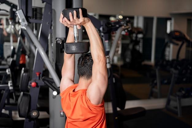 Azjatycki człowiek pracuje w siłowni fitness