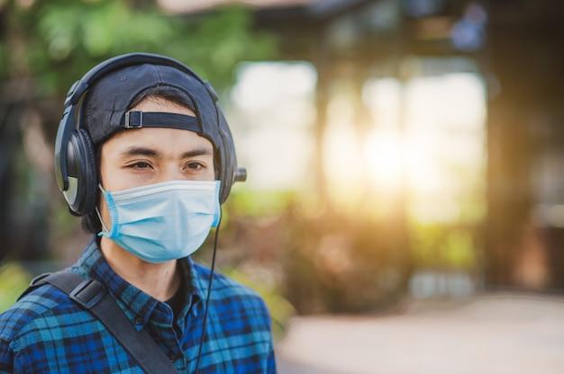 Azjatycki człowiek słuchanie muzyki telefon głowy noszenie maski na zewnątrz nowy normalny styl życia