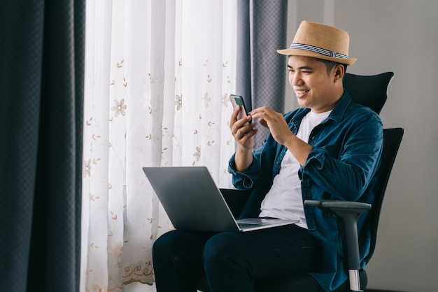 Azjatycki człowiek szczęśliwy zrelaksowany siedzi i rozmawia z mediami społecznościowymi za pomocą telefonu komórkowego, koncepcja pracy z domu