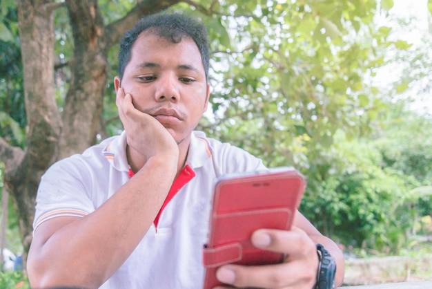 Azjatycki człowiek szuka inteligentny telefon. czuje się znudzony.