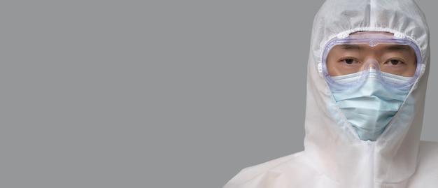 Azjatycki człowiek ubrany w strój ochronny, maski medyczne i gogle na szarym tle.