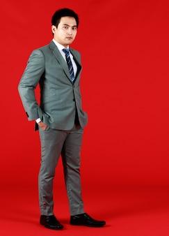 Azjatycki człowiek ubrany w szary garnitur, trzymając rękę odebrać spodnie w czerwonym tle. biznesmen o stojącej osobowości i dobrze ubrany, dążący do pracy.