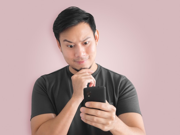 Azjatycki człowiek używa smartfona. czarny t-shirt opłakuje króla tajlandii.