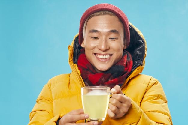 Azjatycki człowiek w ciepłe zimowe ubrania i gorącą herbatę