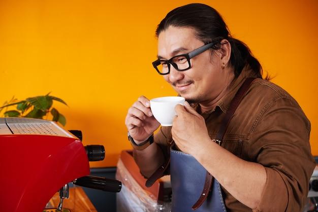 Azjatycki człowiek w fartuch stojący obok ekspresu do kawy, trzymając filiżankę i wąchając kawę
