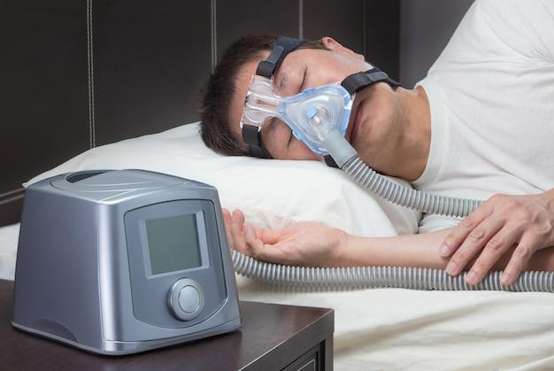 Azjatycki człowiek z bezdechu sennego za pomocą maszyny cpap