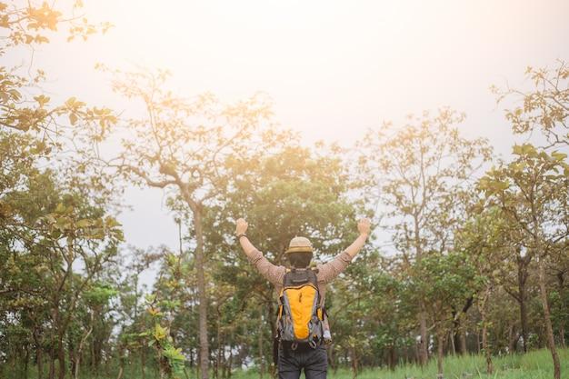 Azjatycki człowiek zrelaksować się na charakter, podróżnik podniósł ramiona i cieszyć się piękną przyrodą