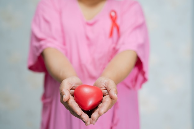Azjatycki dama kobieta pacjenta trzymając w ręku czerwone serce w szpitalu, symbol światowego dnia raka piersi.