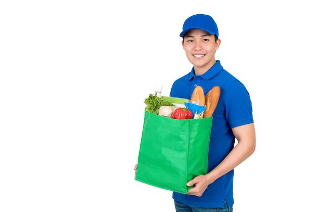 Azjatycki doręczeniowego mężczyzna przewożenia sklepy spożywczy w zielonej reusable torbie