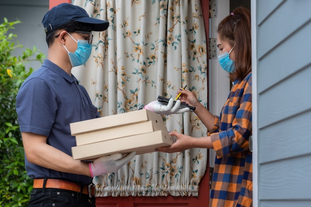 Azjatycki doręczeniowego mężczyzna wysyłki pojęcie młoda kobieta podpisuje wewnątrz cyfrowego telefon komórkowego po otrzymywać pakuneczek i dostarcza jedzenie na wynos od kuriera w domu. usługa kwarantanna pandemiczny wirus koronawirusa.