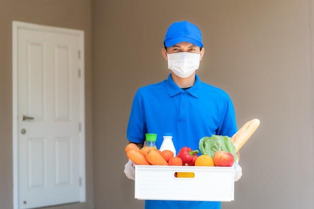 Azjatycki doręczeniowy mężczyzna jest ubranym maskę i rękawiczkę z pudełkiem spożywczym pudełko z jedzeniem, owoc, warzywem i napojem stoi przed domem klienta w czasie odosobnienia domu.