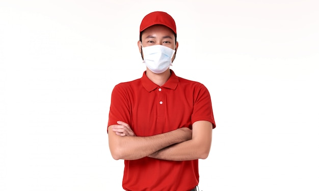 Azjatycki doręczeniowy mężczyzna jest ubranym twarzy maskę w czerwień mundurze odizolowywającym nad białym tłem.