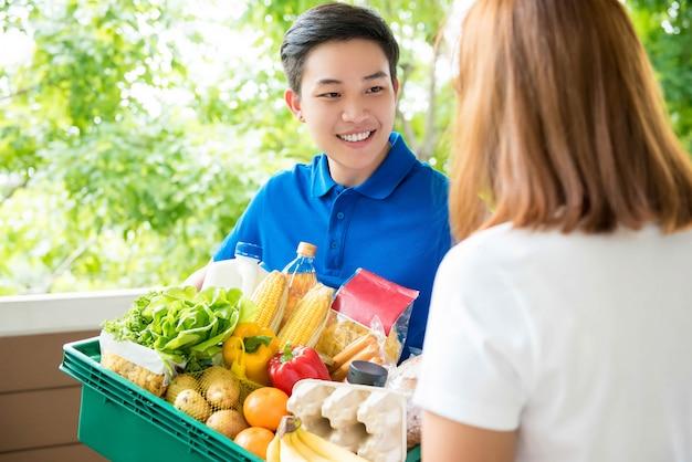 Azjatycki doręczeniowy mężczyzna przekazuje jedzenie klientowi przy jej rezydencją