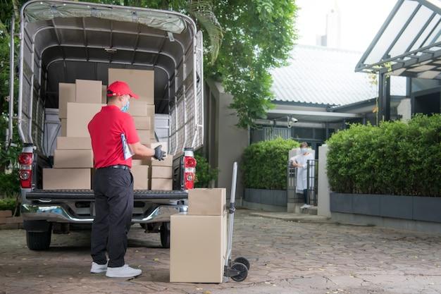 Azjatycki doręczyciel w masce i rękawiczkach w czerwonym mundurze dostarcza paczkę do odbiorcy podczas wybuchu epidemii covid-19