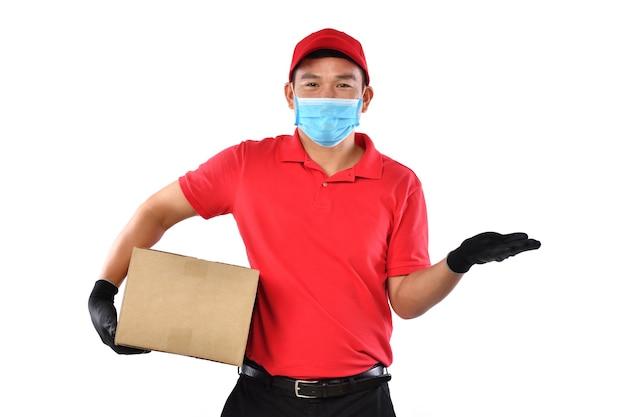 Azjatycki doręczyciel w masce i rękawiczkach w czerwonym mundurze dostarczający paczkę na białym tle podczas wybuchu covid-19