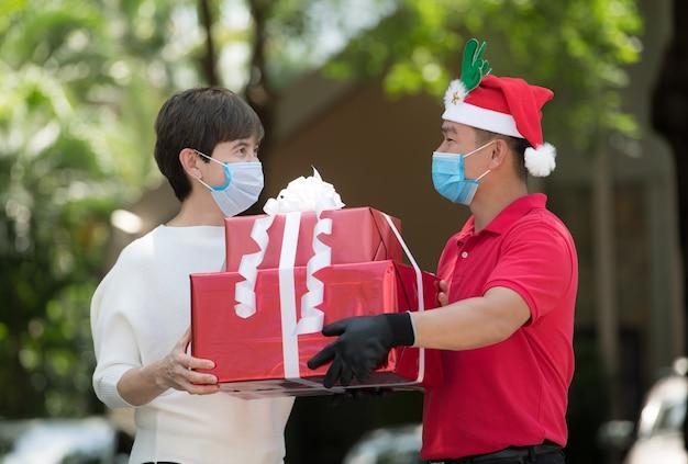 Azjatycki dostawca w masce i rękawiczkach w czerwonym mundurze i świątecznej czapce dostarcza prezenty i pudełka na prezenty kobiecie podczas wybuchu epidemii covid-19 na święta bożego narodzenia