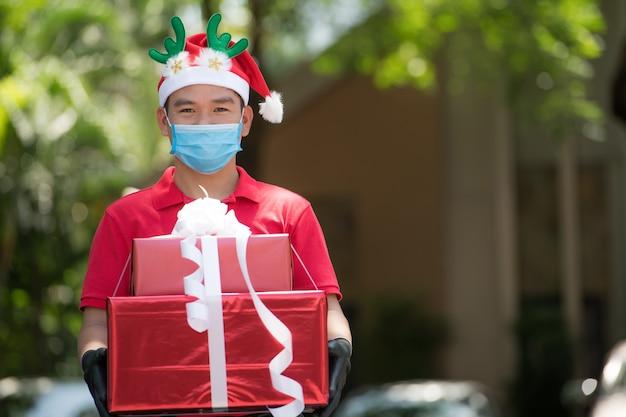 Azjatycki dostawca w masce i rękawiczkach w czerwonym mundurze i świątecznej czapce dostarcza prezenty i pudełka z prezentami podczas wybuchu epidemii covid-19 na festiwal bożonarodzeniowy