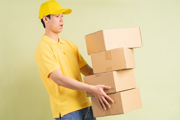Azjatycki dostawczyni trzyma ze sobą karton i biegnie, aby dostarczyć towar