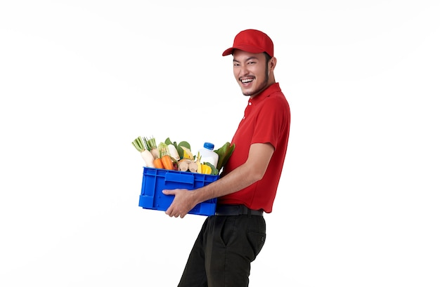 Azjatycki dostawy mężczyzna ubrany w czerwony mundur trzymając kosz świeżej żywności na białym tle nad białą ścianą.