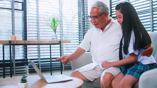 Azjatycki dziadek i wnuczka spędzają razem czas w salonie. szczęśliwy starszy mężczyzna z małą dziewczynką za pomocą laptopa na kanapie w domu.
