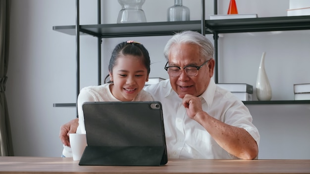 Azjatycki dziadek i wnuczka spędzają razem czas w salonie. szczęśliwy starszy mężczyzna z małą dziewczynką za pomocą tabletu na stole w domu.