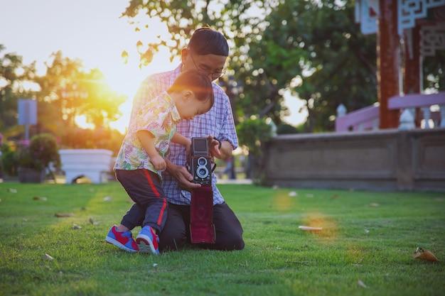 Azjatycki dziadek i wnuk zrobili zdjęcie razem z aparatem retro na zewnątrz