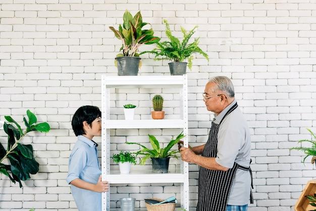 Azjatycki dziadek na emeryturze i jego wnuk z uśmiechem spędzają razem czas, ciesząc się pielęgnacją roślin w wewnętrznym ogrodzie. więź rodzinna między starymi i młodymi.