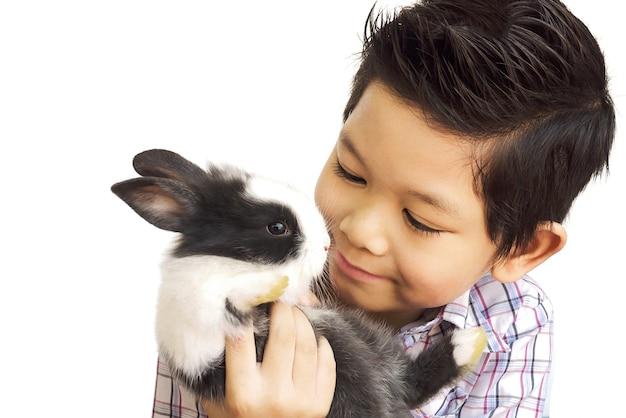 Azjatycki dzieciak bawić się z uroczym dziecko królikiem odizolowywającym nad bielem
