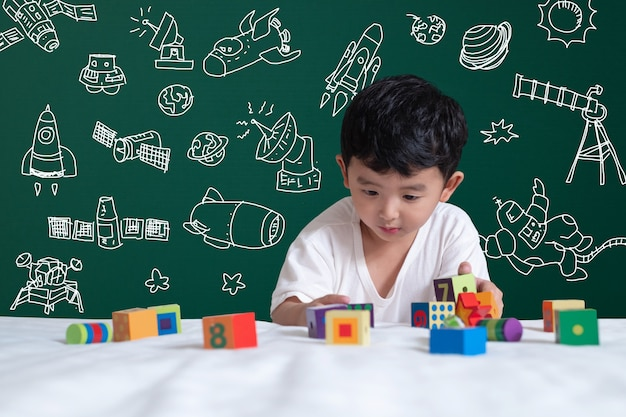 Azjatycki dzieciak bawić się zabawkę z naukową i kosmiczną przygodą, ręka rysująca