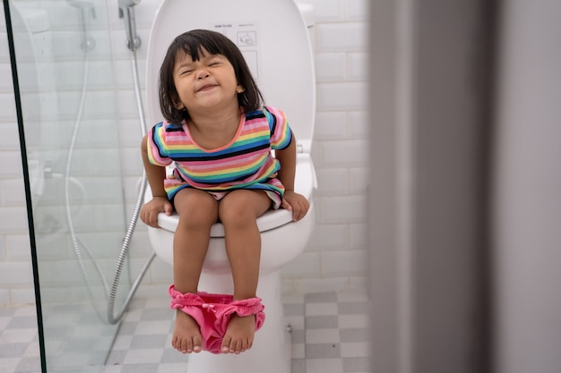 Azjatycki dzieciak pcha mocno, siedząc w toalecie