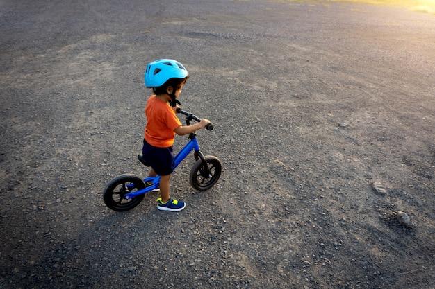 Azjatycki dzieciak pierwszy dzień gra na rowerze równowagi.