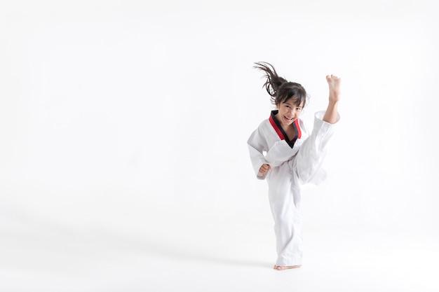 Azjatycki dzieciak taekwondo kopie w białym studiu