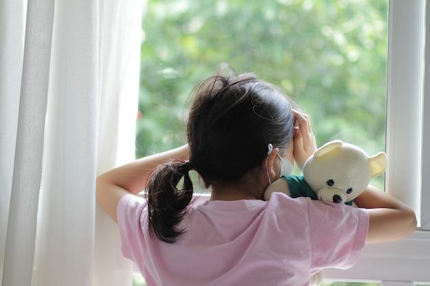 Azjatycki dzieciak w wieku 6 lub 7 lat ubrany w maskę medyczną. mała dziewczynka stojąca przy oknie i wyglądająca na zewnątrz. wygląda na smutną, znudzoną. może chorować lub poddać się kwarantannie na podstawie choroby coronavirus 19 (covid-19).