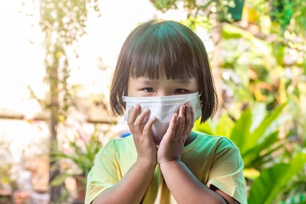 Azjatycki dzieciak z maską do ochrony przed wirusem i ograniczenia rozprzestrzeniania się koronawirusa