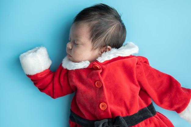 Azjatycki dziecko nowonarodzony na santa claus munduru dosypianiu z czerwieni pudełka teraźniejszością i czerwonym kapeluszem na błękitnym tle