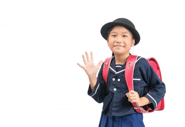 Azjatycki dziewczyna uczeń chodzi do szkoły i macha do widzenia
