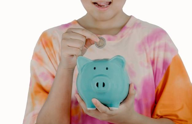 Azjatycki dziewczynka ręka wkładanie monety do niebieskiej skarbonki, naucz się oszczędzać na przyszłą koncepcję.