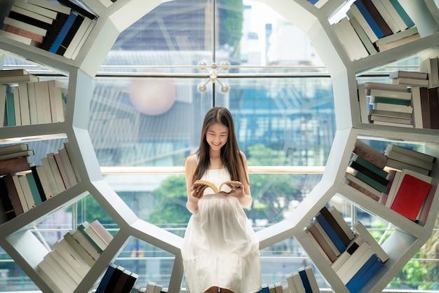Azjatycki dziewczyny czytanie na półka na książki w bibliotece w jej uniwersytecie