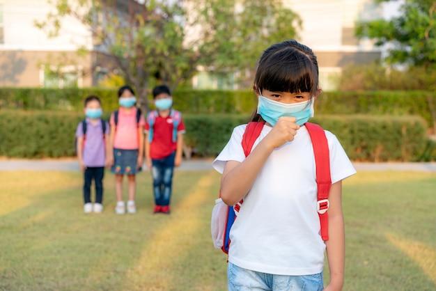 Azjatycki dziewczyny preschool dziecka uczeń jest ubranym zdrową twarzy maskę