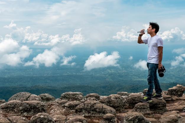 Azjatycki fotograf stojąc na skalistej górze pije wodę z plastikowej butelki