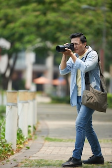 Azjatycki fotograf z profesjonalnym aparatem fotografującym w parku miejskim