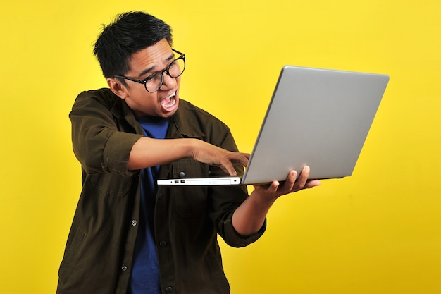 Azjatycki freelancer online jest bardzo zły przed swoim laptopem, otrzymuje złą wiadomość od klienta, odizolowany na żółto