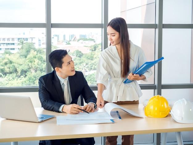 Azjatycki główny architekt lub inżynier w garniturze i młoda sekretarka rozmawiają na temat planu z laptopem i biało-żółtymi twardymi kapeluszami na biurku na ogromnym szklanym oknie w biurze.