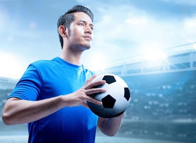 Azjatycki gracza futbolu mężczyzna trzyma piłkę na boisku piłkarskim