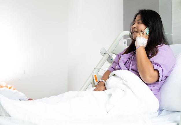 Azjatycki gruba kobieta pacjenta za pomocą smartfona na łóżku w nowym centrum medycznym. sala pooperacyjna z łóżkami i wygodną medycyną