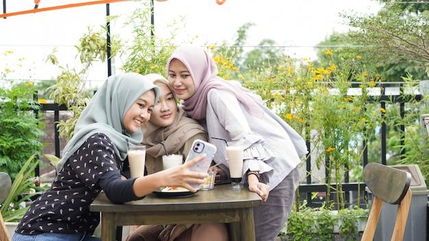 Azjatycki hidżab kobieta grupowe selfie w kawiarni z przyjacielem